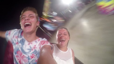 4k Two teenagers shouting while turning on ride at amusement park