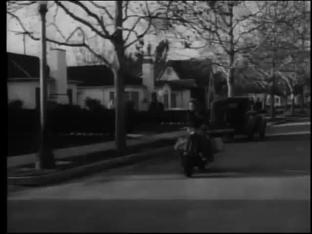 Paperboy on scooter delivering newspapers,1950s