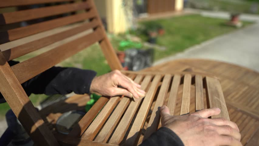Personal perspective of  carpenter's hand restoring a wooden chair with sandpaper. Garden furniture. POV.