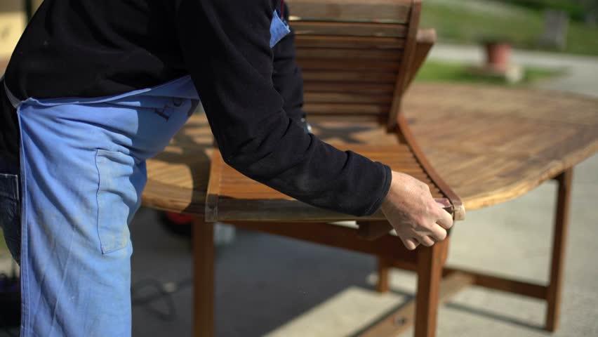Closeup of restoring a wooden chair with sandpaper. Garden furniture.