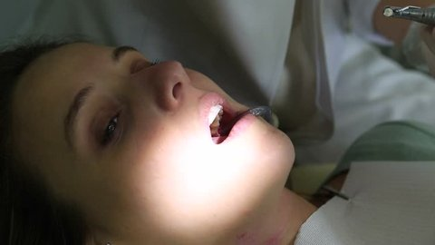 Dentist. Close up of female with open mouth during oral checkup at the dentist.
