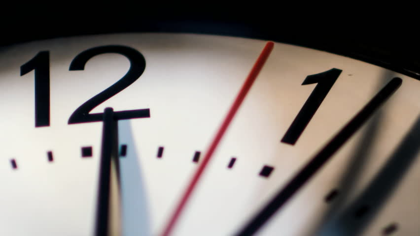 Time passing on classic wall clock face closeup