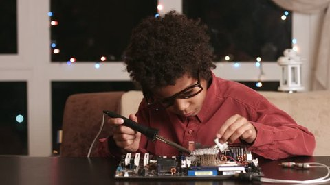 Afro boy soldering motherboard. Darkskinned boy solders motherboard. I know what to do. Very specific hobby.