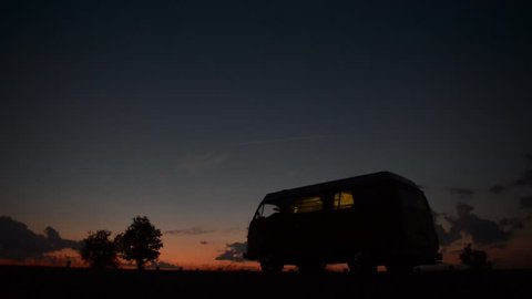 A 1977 volkswagen bus starts it's engine and drives off during a sunset.