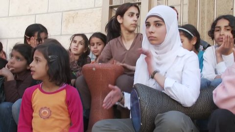 WEST BANK BARRIER, PALESTINIAN OCCUPIED TERRITORIES, ISRAEL - APRIL 1, 2008: Young Palestinian female students play music on drums