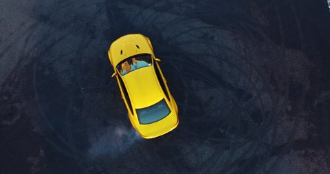Top view of the golden car drifting on the road. ?ar makes a few laps. Shooting with a drone in 4k.
