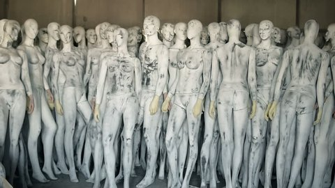 Creepy naked female and male mannequins are standing in factory depot