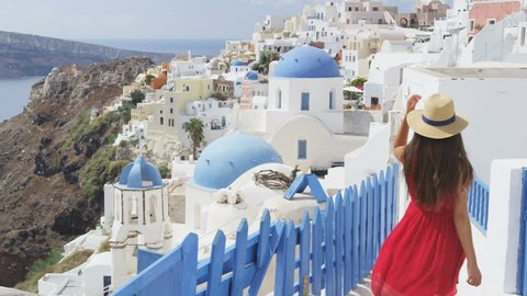 Tourist travel woman in Oia, Santorini, Greece. Happy young woman walking on stairs by famous blue dome church landmark destination. Beautiful girl in red dress on visiting the Greek island.