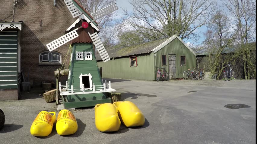 Outside a clog farm showing large yellow wooden shoes and small windmill amazing Dutch traditional klompen workshop typical for Netherlands Holland tourist visit attraction near Amsterdam Europe 4k