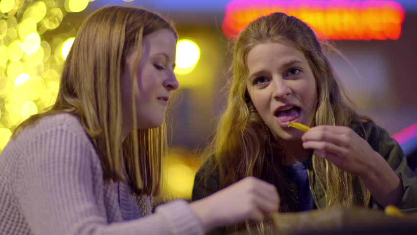 Teen Girls Hang Out At Night And Enjoy Eating Fast Food French Fries