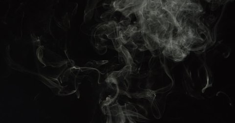 Wisps of turbulent smoke from a candle or cigarette rise into frame and swirl in slow motion on black background, ALPHA MATTE