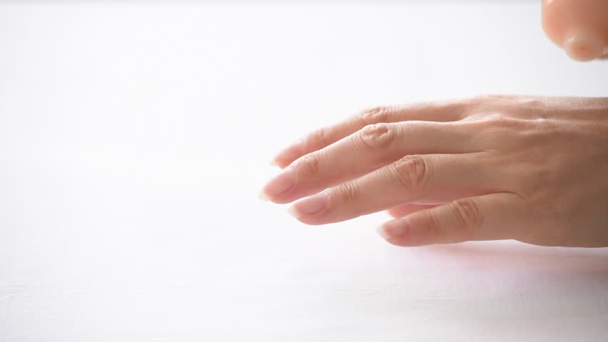 Close up shot of a woman`s hands spreading a cream over the fingers  #15677989