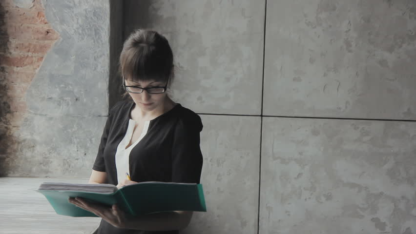 Business girl with green folder in hand writes | Shutterstock HD Video #15683599
