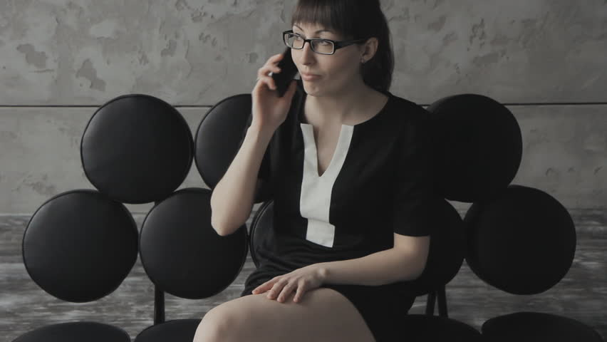 Business woman on the couch, talking on the phone, smiling | Shutterstock HD Video #15683623