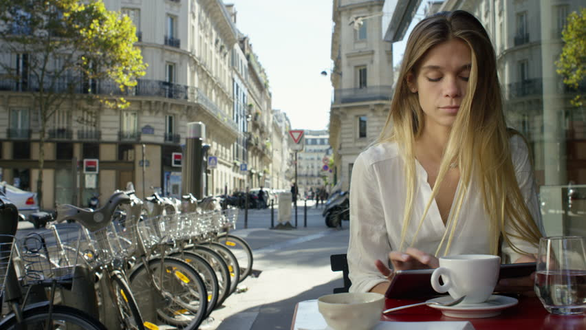 Young Lady working on her tablet while at a local cafe. Paris, France | Shutterstock HD Video #15693049
