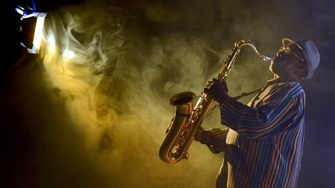 African jazz musician in tuxedo playing the saxophone.