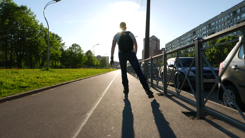 SAINT-PETERSBURG, RUSSIA - MAY 28, 2015: Unidentified man ride on in-line skates at small lane, against bright sunlight. Camera follow behind, quickly move after, hide shadow from person body #15717019