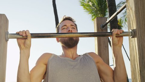 Pull-up strength training exercise - fitness man working out his arm muscles on outdoor beach gym doing chin-ups / pull-ups as part of a crossfit workout routine.