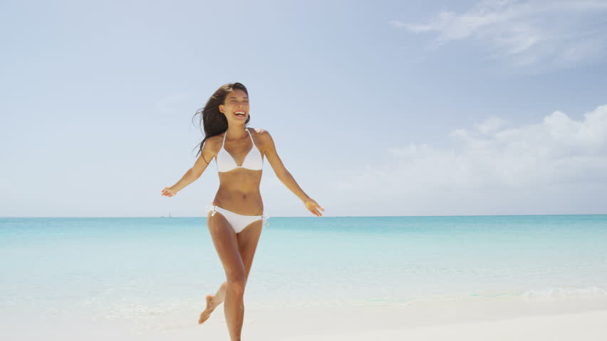 Beach bikini woman carefree running in freedom fun. Joyful happy Asian girl relaxing showing joy and happiness in slim body for weight loss diet concept on perfect white sand. Throwing beach hat. | Shutterstock HD Video #15766009