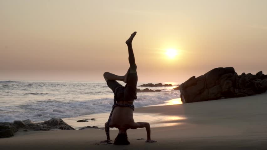 Caucasian man doing head stand on the beach at sunset | Shutterstock HD Video #15777838
