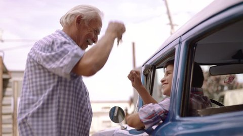 Family and generation gap. Old grandpa spending time with happy boy. The senior man gives the keys of a vintage car from the 1950s to the preteen child sitting inside