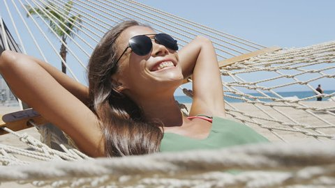 Happy beach vacation woman putting on aviator sunglasses relaxing lying down on outdoor patio hammock tanning smiling happy sunbathing during summer holidays. Asian woman on tropical vacations.