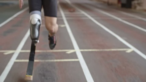 Tilt up of inspiring amputee athlete with artificial leg running on track at indoor stadium in slow motion