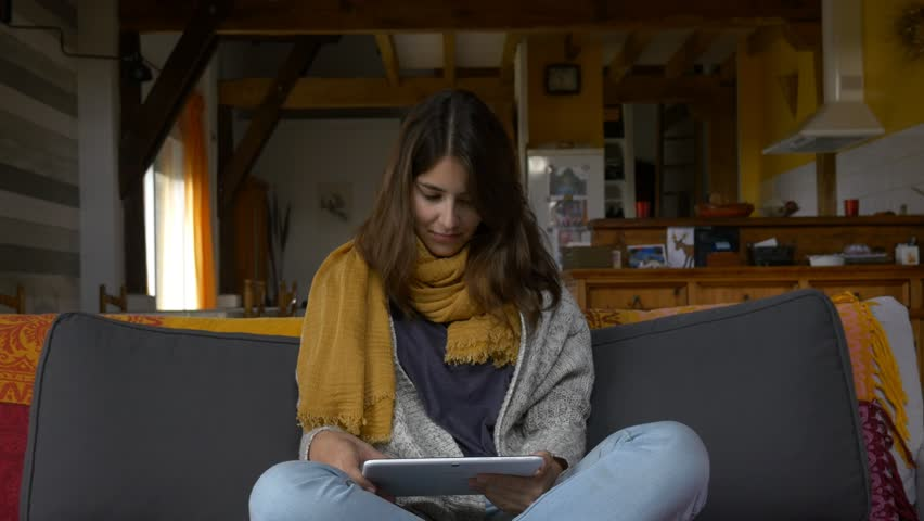 Young attractive woman using tablet pc ipad 4k in beautiful countryside rural house inside rustic style modern girl hipster slider tracking shot sitting in sofa