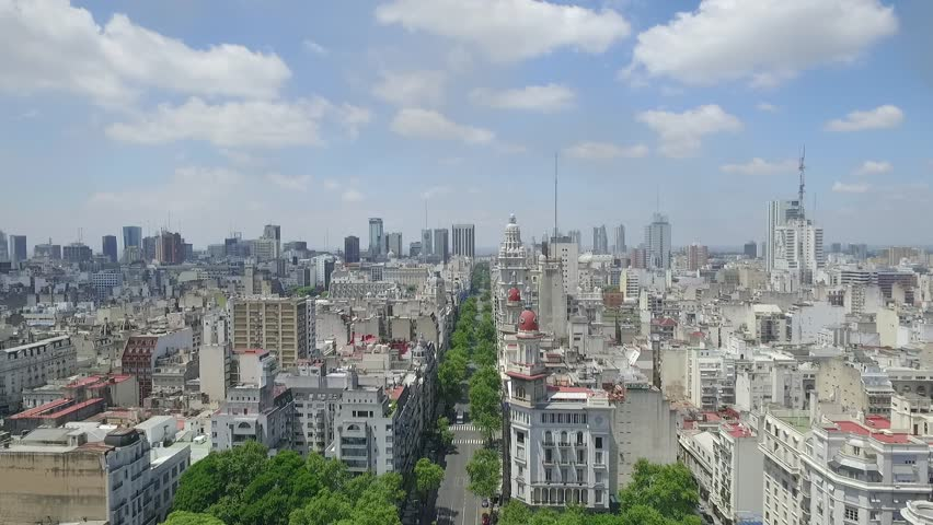 Aerial Drone Scene Of City Landscape. Travelling out of May Avenue. The Camera Goes Backwards. Cityscape, Towers, Trees And Buildings Background. Avenida de Mayo - Buenos Aires-Argentina