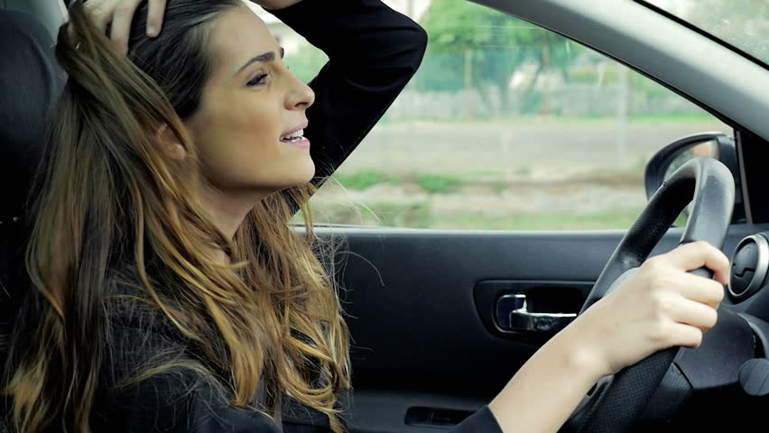Woman with long hair singing and driving happy in car slow motion
