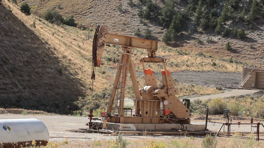 Oil well pumping crude from deep valley between mountains in central Utah. Propane motor powers the pump that extracts the oil. Fast motion timelapse.