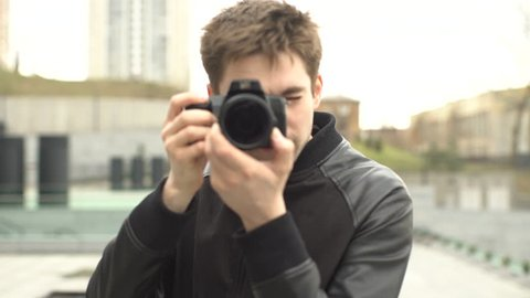 Handsome Man Photographer Photographs , Turns the Focus, the Camera Selects the Purpose of Shooting , Viewing the Result on the Screen Shot , Photoshoot, Man in a Black Jacket With a Camera