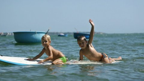 Happy smiling adorable little children enjoying blue sea surfboarding on surfboard, waving hands and jumping into the water on summer vacation in slow motion.