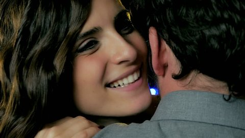 Beautiful young woman whispering words of love in the ear of boyfriend full of happiness