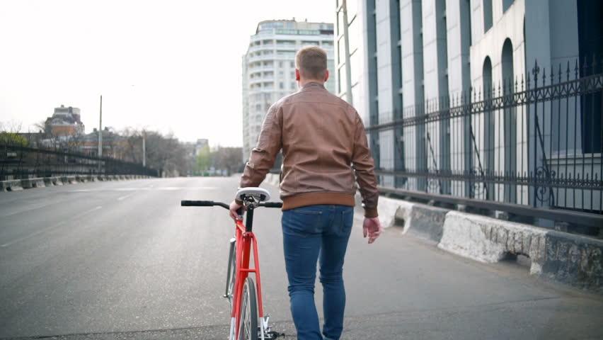 male cyclist walks near the bike in the street slow motion