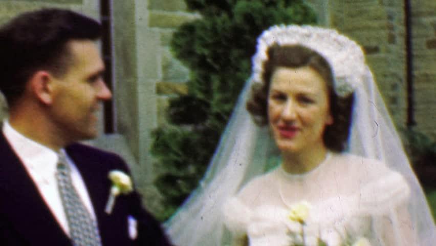 WINNIPEG, MANITOBA 1961: Happy wedding couple excited outside stone classic church.
