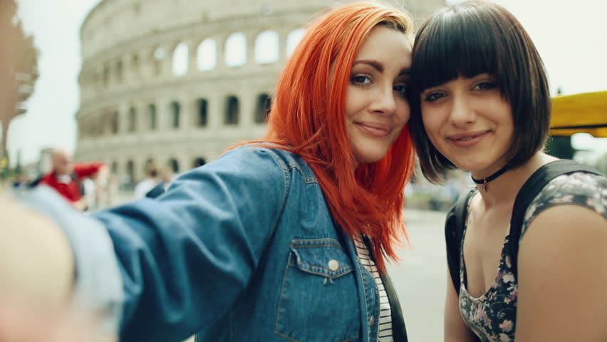 Tourist Women Take A Selfie In Rome By The Coliseum
