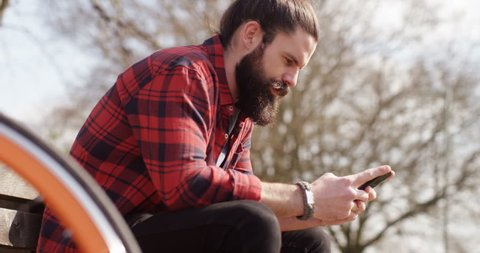 4k, handsome man typing text message in a park on his mobile phone while taking a break from cycling.