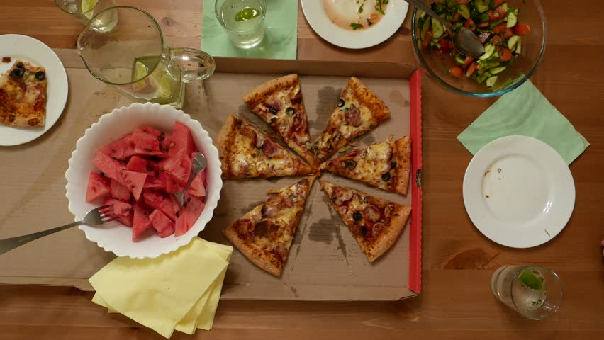 Small party served table, man hand pick up piece of pizza from delivery service. Cut watermelon, salad bowl, lime drink in glass. Three people around wooden desk, top point view from above