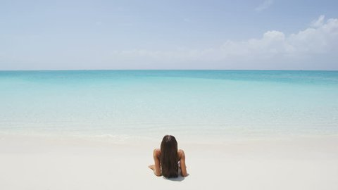 Beach travel vacation holidays. Woman enjoying sunbathing looking at ocean lying down in perfect white sand relaxing after swimming in amazing turquoise water. Serene nature. RED EPIC SLOW MOTION