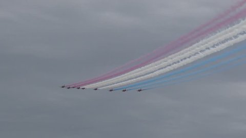 The RAF's Red Arrows perform at an airshow, flying in formation and climbing at high altitude. They begin to form their trademark diamond formation.