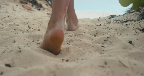 Girl feet walking on the beach in between palm trees in slow-motion in the Caribbean. Shot on RED Cinema Camera in 4K, crop, rotate and zoom easily. Prores HQ codec.