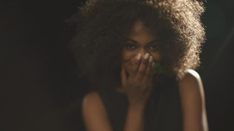 Beautiful exotic shy young black woman covers face by hand and flirting
