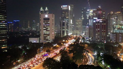 Traffic rushes through Jakarta main avenue, Jalan Sudirman, in the heart of the city business district at night