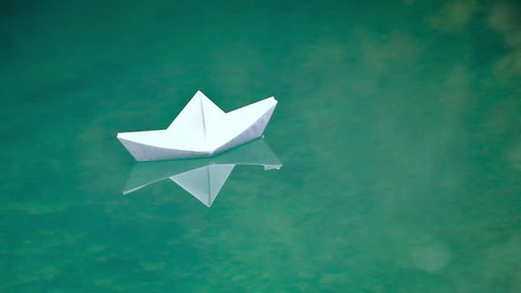 looping video of a paper boat floating in some water