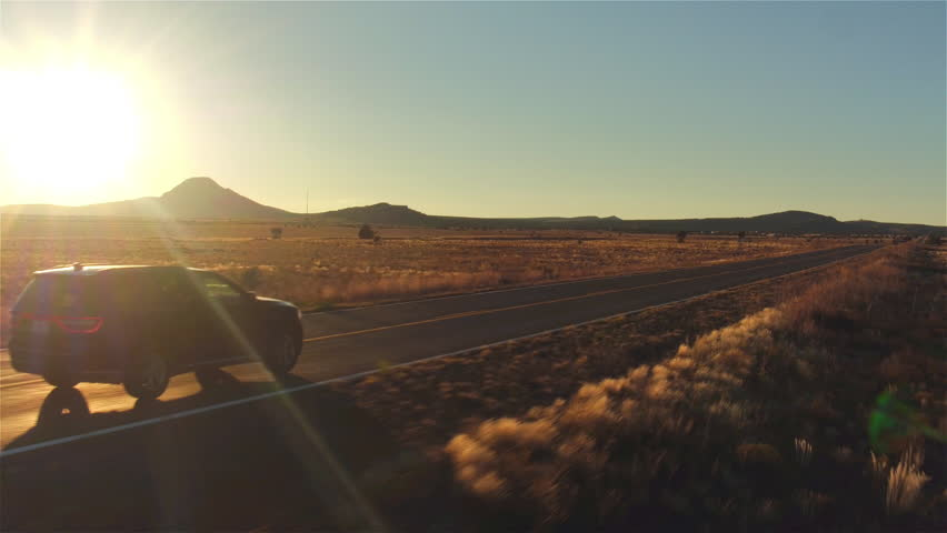 AERIAL: Black SUV car driving along empty country road at golden summer sunset. People traveling, road trip on historic Route 66 through beautiful meadow desert scenery in sunny summer | Shutterstock HD Video #16115923