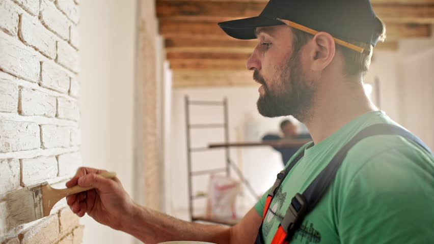 Renovation: man painting a wall, enjoying the work. Slow motion