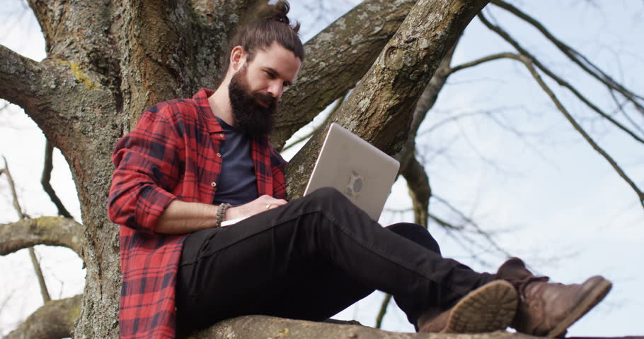 4k young man sitting on a tree trunk away from hustle and bustle of a city and working on his laptop. | Shutterstock HD Video #16143139