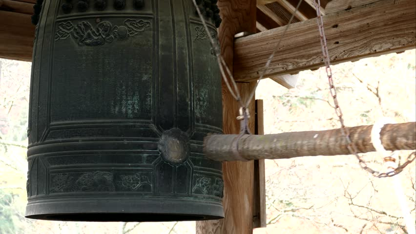 KYOTO, JAPAN -NOV 22, 2015: Log hitting the old large bronze bell tower in Yoshiminedera temple, This belfry was constructed in 1685 and the belfry is rung every december in Kyoto, Japan