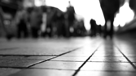 Low angle shot of anonymous crowd of people walking over zebra crossing. Shallow depth of field. People in blur. Slow motion footage. Vintage color grading. Black and white. Grayscale. 4k UHD Ultra HD
